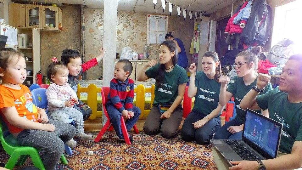 A group of female volunteers working with children in Mongolia demonstrate personal hygiene at a care centre.